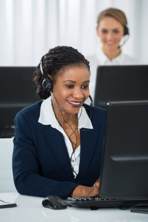 Employee With Headset Working On Computer