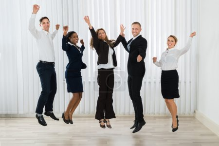 Photo for Group Of Professional Businesspeople Jumping In Joy At Workplace - Royalty Free Image