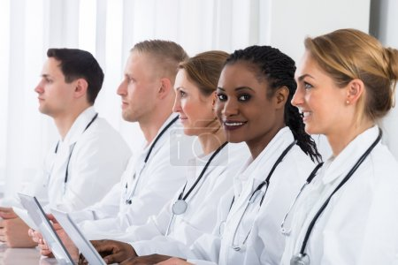 Photo for Group Of Doctors In Labcoat Using Laptop At Desk - Royalty Free Image