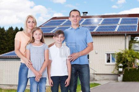 Foto de Retrato de una familia feliz de pie fuera de su casa con paneles solares en el techo - Imagen libre de derechos
