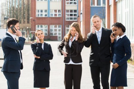 Businesspeople Talking On Mobile Phones