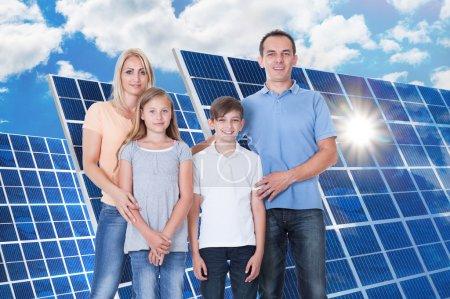 Foto de Retrato de una familia sonriente de pie frente al panel solar - Imagen libre de derechos
