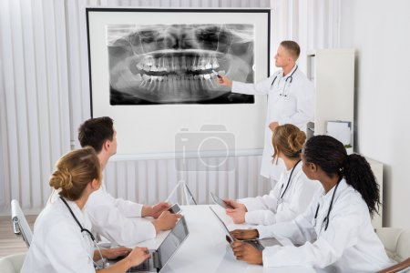 Photo for Young Male Doctor Explaining Human Teeth X-ray To His Colleagues - Royalty Free Image