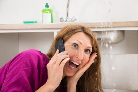 Photo pour Gros plan de la femme appelant au plombier alors que l'eau fuit du naufrage - image libre de droit