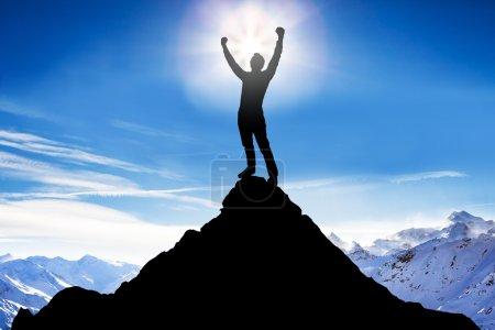 Photo pour Silhouette d'un triomphe après avoir réussi l'escalade contre les montagnes enneigées - image libre de droit