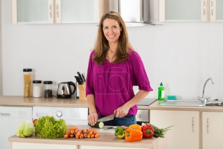 Photo for Smiling Woman Cutting Vegetables On Chopping Board In Kitchen - Royalty Free Image