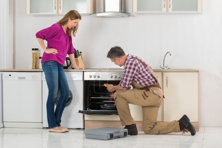 Photo for Woman Looking Am Male Worker Checking Oven With Digital Multi Meter In Kitchen - Royalty Free Image
