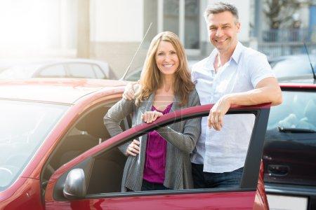Photo pour Portrait de couple heureux debout avec leur voiture rouge nouvellement acheté - image libre de droit