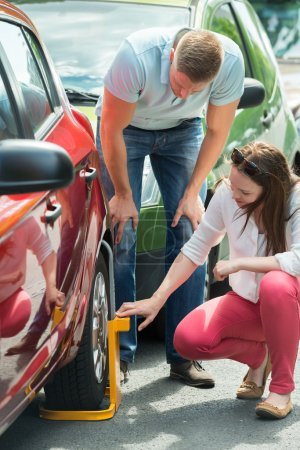 Photo for Young Couple Looking At Wheel Lock On Their Illegally Parked Car - Royalty Free Image