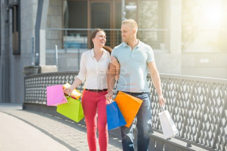 Photo for Young Happy Couple Walking On Bridge With Multi-colored Shopping Bags - Royalty Free Image