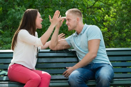 Photo for Young Couple Sitting On Bench Quarreling With Each Other At Park - Royalty Free Image