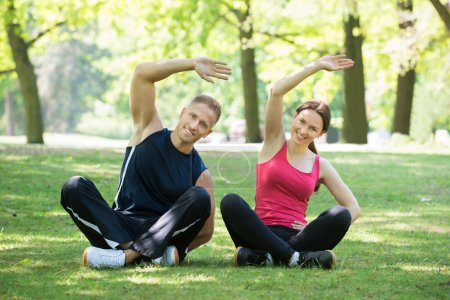 Photo pour Joyeux jeune couple faisant de l'exercice dans le parc le matin - image libre de droit