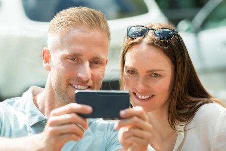 Couple Taking Picture Using Mobile Phone