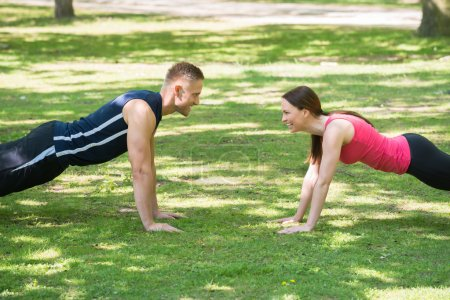 Couple Doing Push-ups In Park
