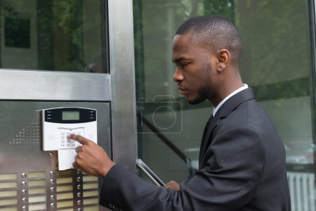 Businessman Entering Code In Security System
