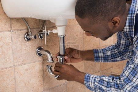 Plumber Hand Fixing Sink In Bathroom