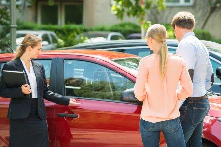 Photo pour Confiant concessionnaire femelle jeune montrant la nouvelle voiture rouge pour Couple - image libre de droit