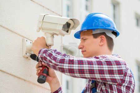 Foto de Joven masculino técnico instalación de cámara en la pared con un destornillador - Imagen libre de derechos