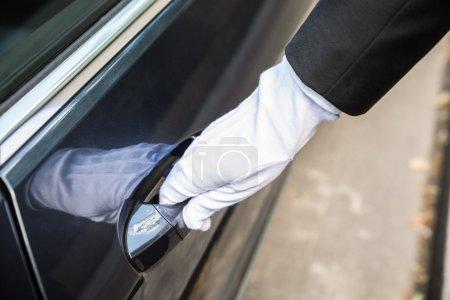 Photo pour Gros plan d'un chauffeur tirant une poignée de porte de voiture - image libre de droit