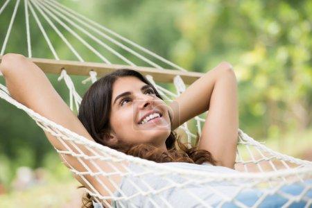 Photo pour Gros plan d'une jeune femme heureuse allongée dans un hamac - image libre de droit