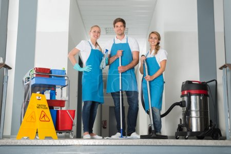 Portrait Of Janitors Holding Cleaning Equipments