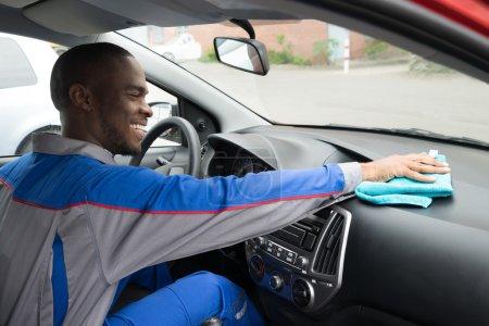 Photo pour Happy African Worker nettoyage intérieur de voiture avec tissu - image libre de droit