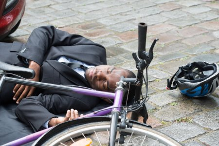 Photo for Young African Male Cyclist Lying On Street After Accident - Royalty Free Image