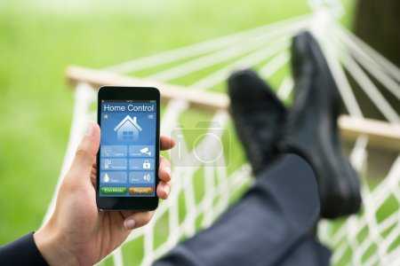 Man With Mobile Phone Showing Home Control System