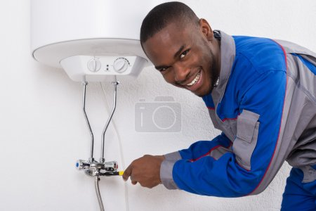 Worker Repairing Electric Boiler With Wrench
