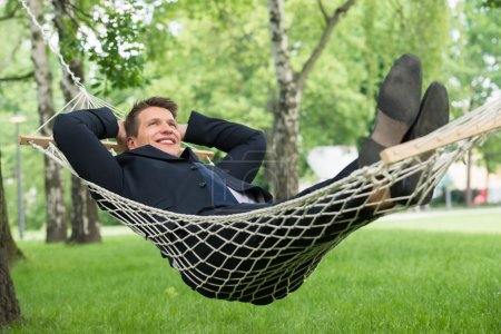 Photo for Happy Young Businessman Lying In Hammock At Park - Royalty Free Image