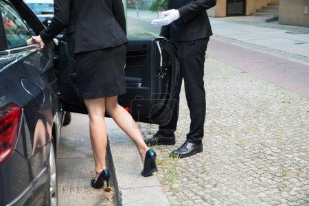 Photo pour Chauffeur masculin ouvrant la porte de la voiture pour la femme d'affaires sur la rue - image libre de droit