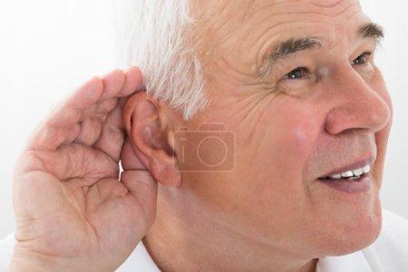 Photo pour Senior homme essayer d'entendre avec la main sur l'oreille - image libre de droit
