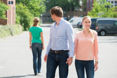 Man Walking With His Girlfriend Looking At Another Woman