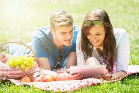 Photo pour Couple heureux en utilisant la tablette numérique tout en étant couché dans le parc - image libre de droit