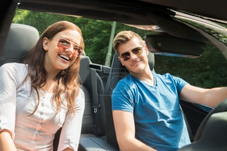 Young Couple In A Car Wearing Sunglasses