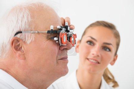 Photo pour Gros plan d'un optométriste vérification Senior masculine Vision patiente avec lunettes d'essai à la clinique ophtalmologique - image libre de droit