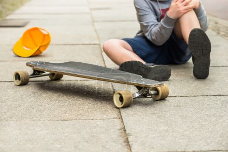 Photo for Boy With Knee Injury Sitting Near Skateboard On Sidewalk - Royalty Free Image