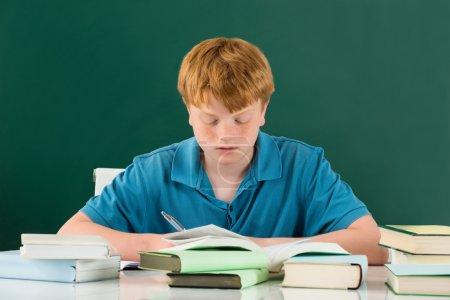 Photo pour Garçon en salle de classe avec des livres sur le bureau contre tableau vert - image libre de droit