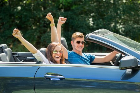 Couple Sitting In A Car Wearing Sunglasses