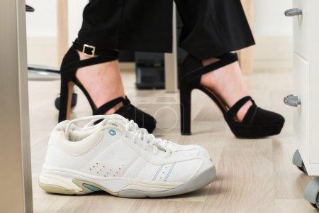 Sport Shoes Besides Businesswoman's Foot