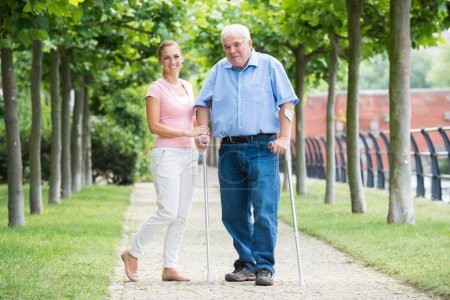 Woman With Her Disabled Father Standing In Park