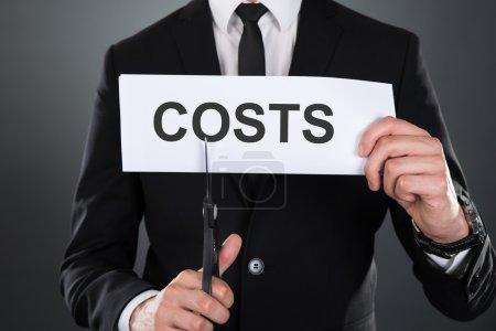 Photo pour Midsection de l'homme d'affaires couper le mot Coûts sur papier avec des ciseaux sur fond gris - image libre de droit