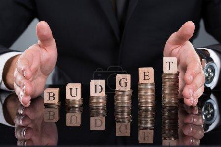 Foto de Cintura del empresario de protección de bloques de presupuesto en monedas apiladas en el escritorio - Imagen libre de derechos