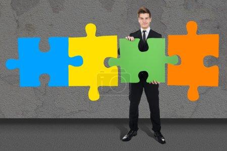 Confident Businessman Solving Jigsaw Puzzle
