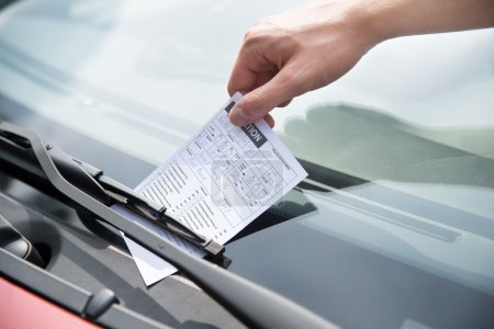 Photo for Close-up of officer's hand putting parking ticket on car windshield - Royalty Free Image