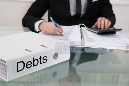 Midsection of businessman calculating debts at des...