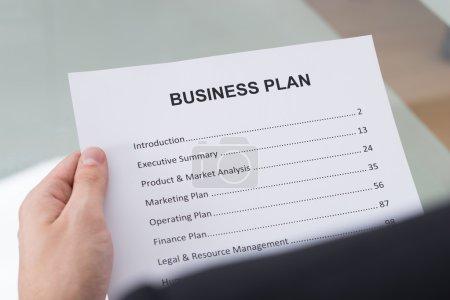 Photo pour Cropped image d'homme d'affaires, lire le document de plan d'affaires au bureau - image libre de droit