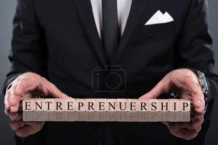 Businessman Showing Entrepreneurship Blocks