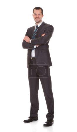 Foto de Full length portrait of confident young businessman standing arms crossed against white background - Imagen libre de derechos