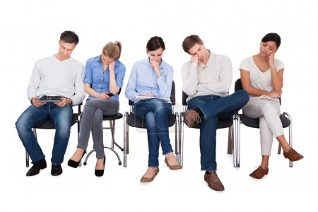 Photo pour Full length of bored businesspeople sitting on chairs against white background - image libre de droit